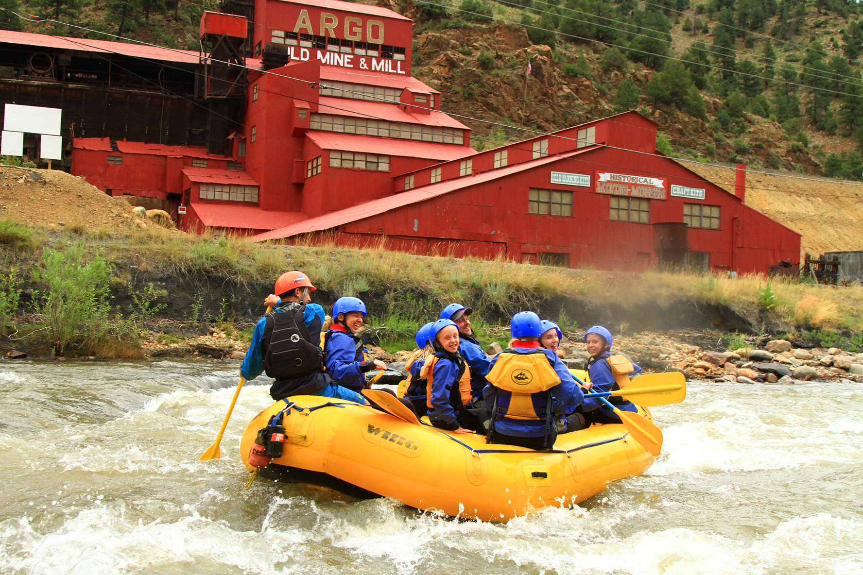 A yellow raft full of people in front of the Argo Mine in Idaho Springs, Colorado